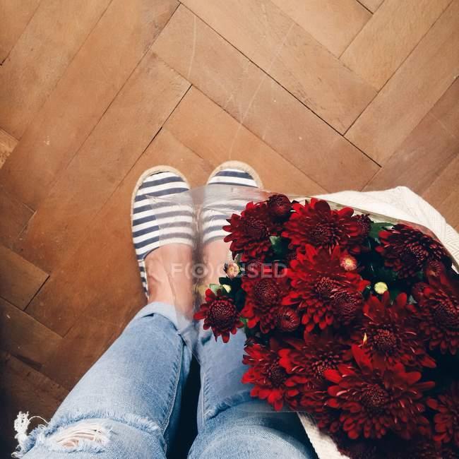 Женские ножки и свежие красные цветы в сумке на деревянном полу — стоковое фото