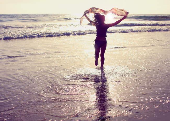 Женщина бежит по пляжу с американским флагом над головой — стоковое фото