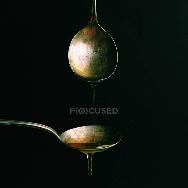 Dripping oil from one spoon onto another against black background — Stock Photo