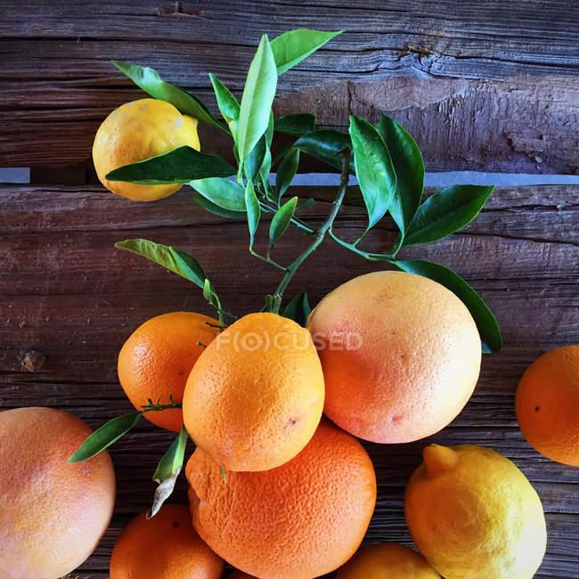 Купи апельсинів і лимонів на дерев'яні таблиці — стокове фото