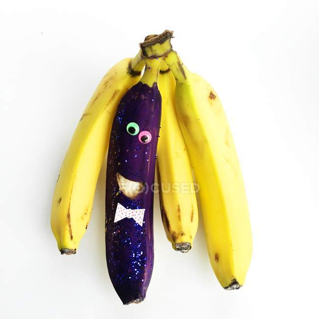 Bunch of bananas with one purple banana character — Stock Photo
