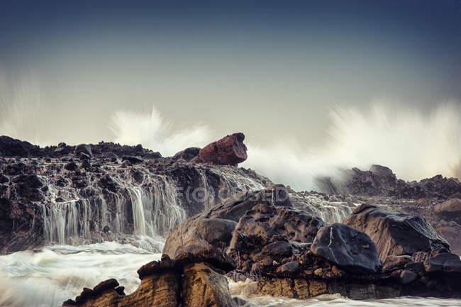 Onde che si infrangono sulle rocce sulla spiaggia, Karang Beureum, Sawarna, Indonesia — Foto stock