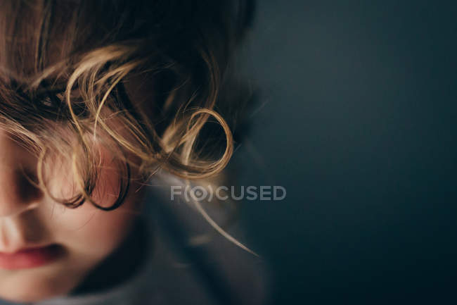 Close-up of girl with curly hair covering face — Stock Photo