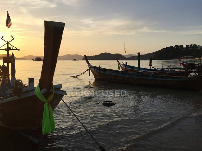 Vista panorámica de barcos amarrados en la playa al atardecer, Phuket, Tailandia - foto de stock