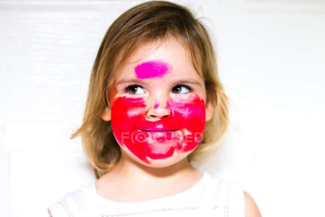 Portrait d'une fille avec du rouge à lèvres sur tout le visage regardant de côté — Photo de stock