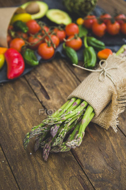 Bunch of fresh asparagus wrapped in linen cloth with fruit and vegetables on wooden table — Stock Photo