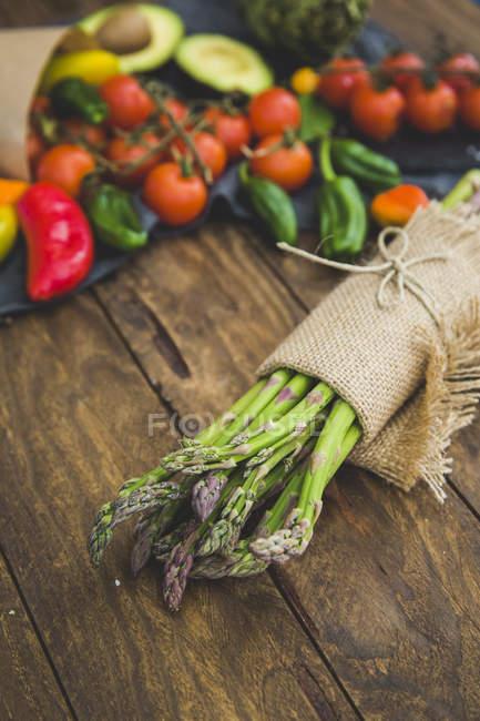 Ramo de espárragos frescos envueltos en tela de lino con frutas y verduras en la mesa de madera - foto de stock