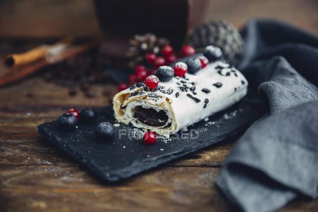 Tentadora de rollo de chocolate con frutas de verano y esparcir azúcar sobre losa de gentrice negro, estilo del patrimonio - foto de stock