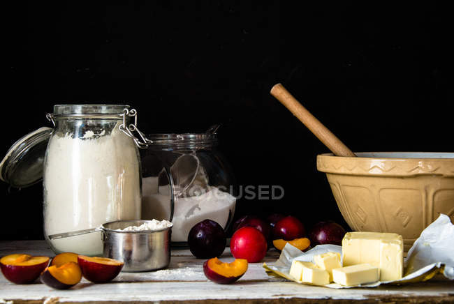 Baking ingredients for a plum cake in kitchen against black background — Stock Photo