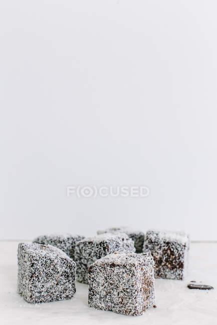 Lamingtons cubiertos de coco contra pared blanca - foto de stock