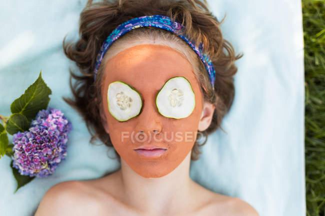 Garçon couché avec masque facial et tranches de concombre sur les yeux — Photo de stock