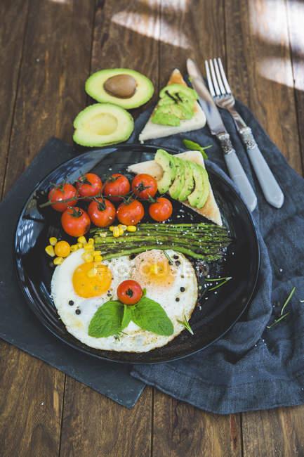 Fried eggs, cherry tomatoes, avocado, asparagus and toast breakfast — Stock Photo