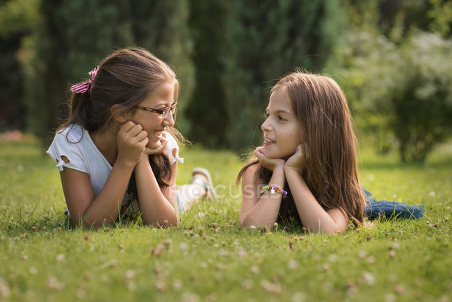 Two Cute Teenage Girls Lying On Green Grass And Looking At Each Other Stock Photo