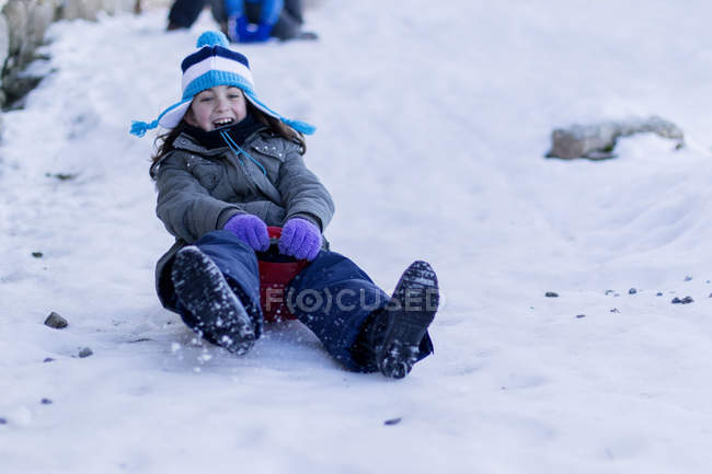 Girl on a sledge sliding down a hill in the snow — Stock Photo