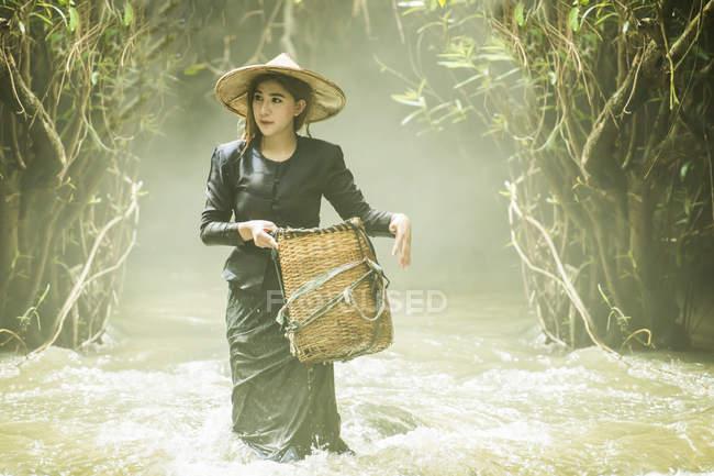 Giovane donna in cerca di pesce nel flusso, Thailandia — Foto stock