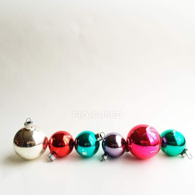 Ornamenti di Natale in fila contro muro bianco — Foto stock