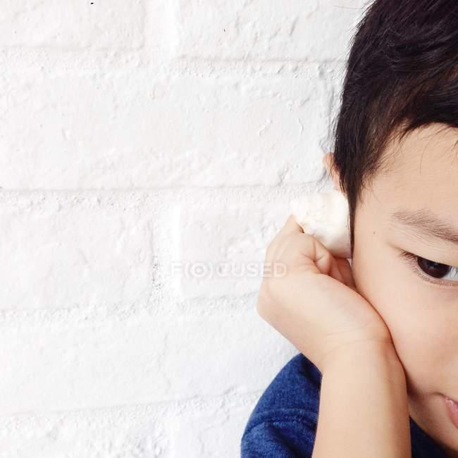 Boy listening to sea in tiny seashell — Stock Photo