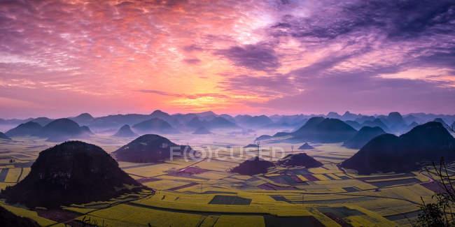 Hermoso amanecer sobre campos de colza oleaginosa, Luoping Yunnan, China - foto de stock
