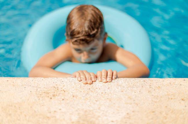 Retrato de menino flutuando no anel de borracha em uma piscina segurando a borda da piscina — Fotografia de Stock