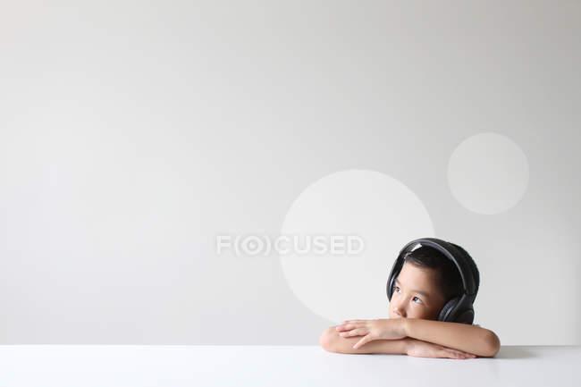 Хлопчик в навушниках, прослуховування музики на білий реєстрації — стокове фото