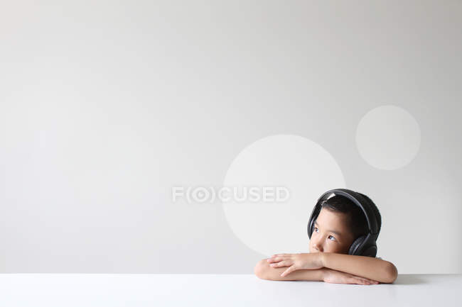 Boy wearing headphones listening to music at white desk — Stock Photo