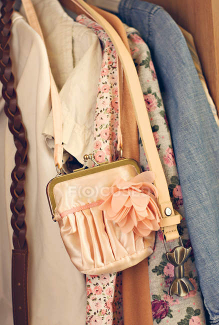 Female clothing and a pink bag in wardrobe — Stock Photo