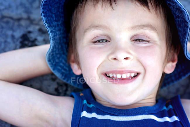 Close-up de menino deitado no chão com as mãos atrás da cabeça — Fotografia de Stock