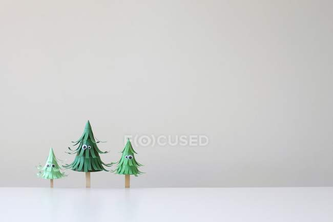 Tre alberi di carta mestiere con gli occhi contro muro bianco — Foto stock