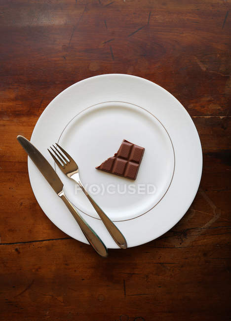 Bar of half eaten chocolate on a plate with a knife and fork — Stock Photo