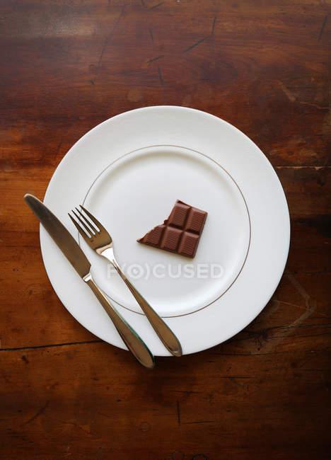 Barra de la mitad comen chocolate en un plato con cuchillo y el tenedor - foto de stock