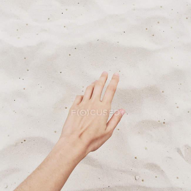 Крупный план руки тянется к песку на пляже, обрезанное изображение — стоковое фото