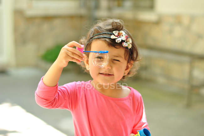 Girl holding a soap bubble wand — Stock Photo