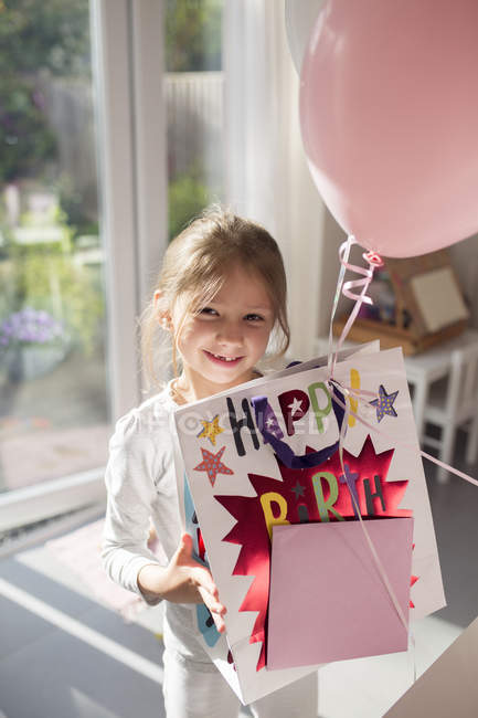 Girl holding birthday present and a balloon — Stock Photo