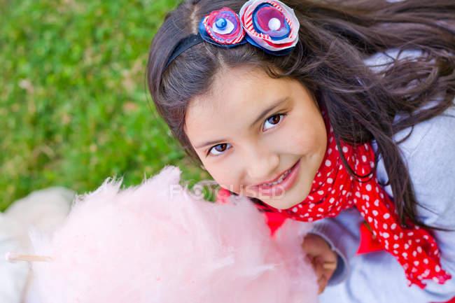 Retrato de menina sorridente segurando algodão doce — Fotografia de Stock