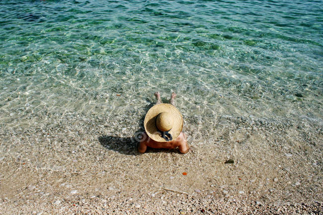 Woman with straw hat sunbathing in water on beach — Stock Photo