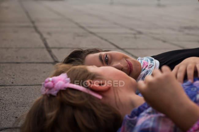 Две милые девушки лежал на полу и глядя друг на друга — стоковое фото