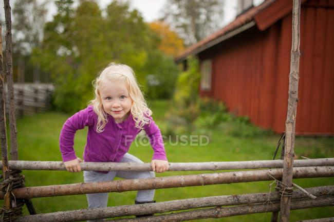 Niña escalando en valla de madera fuera de la casa sueca tradicional - foto de stock