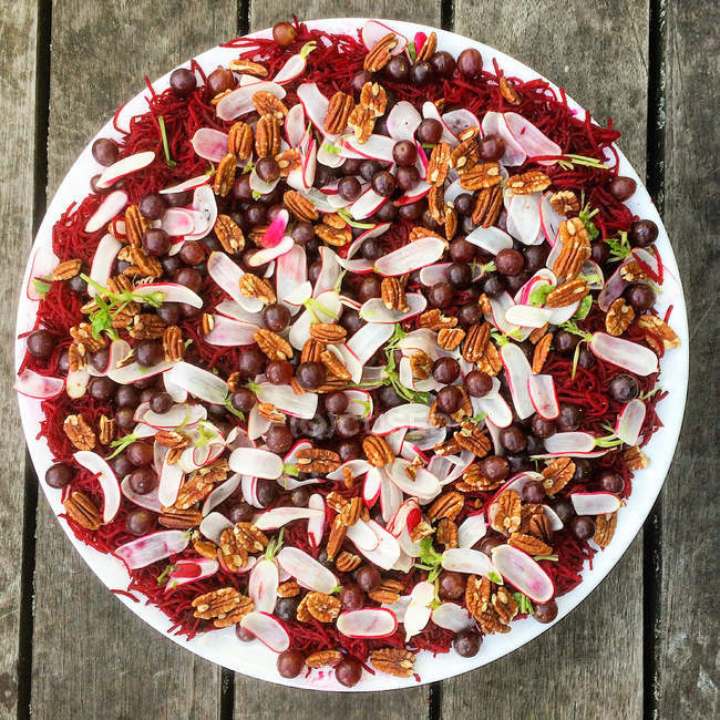 Salat mit Rote Beete, Rettich, Pekannüsse und Blaubeeren auf Platte auf Holz — Stockfoto