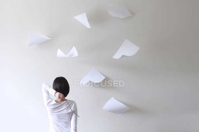 Rear view of woman holding stick behind head with pieces of paper flying around — Stock Photo