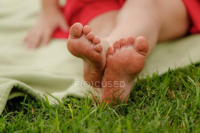 Abgeschnittenes Bild von Mädchenfüßen auf grünem Gras, Nahaufnahme — Stockfoto