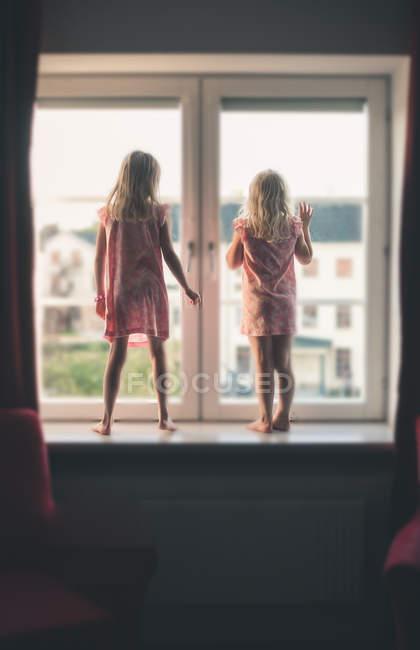 Вид сзади двух девушек, стоящих на подоконнике и выглядывающих в окно — стоковое фото