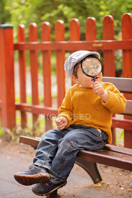 Boy sitting on bench holding a magnifying glass — Stock Photo