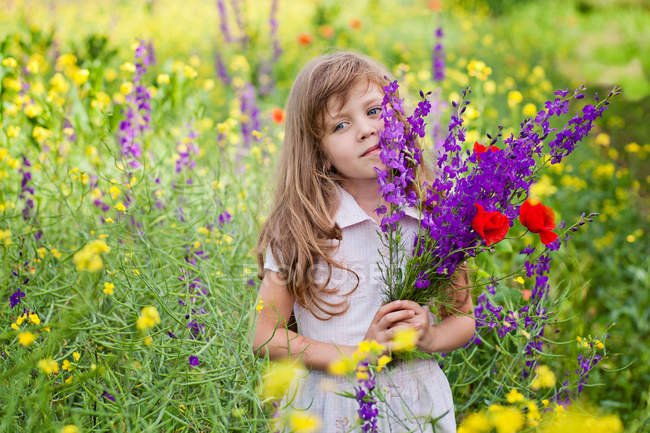 Portrait d'une fille tenant un bouquet de fleurs dans le champ — Photo de stock