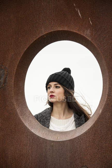 Молода жінка, переглядаючи круглий отвір — стокове фото