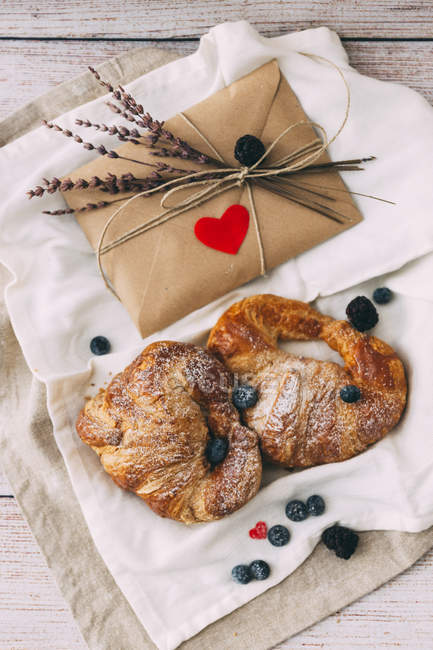 Croissants, blueberries and surprise envelope on fabric on wooden surface — Stock Photo
