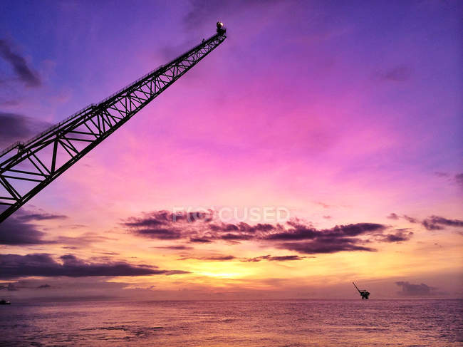 Scenic view of crane on oil rig at purple sunset — Stock Photo