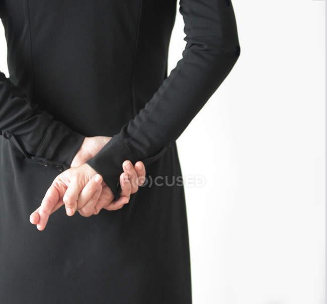 Vue arrière d'une femme avec les doigts croisés derrière le dos — Photo de stock