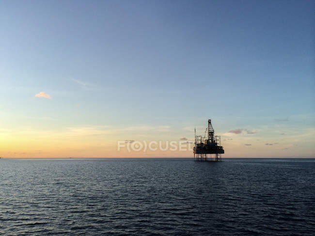 Silhouette of an offshore platform during sunset — Stock Photo