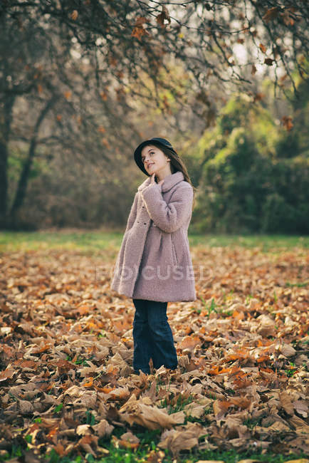 Portrait of a girl looking thoughtful, standing in autumn leaves — Stock Photo