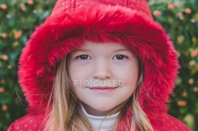 Portrait of a girl wearing a red coat looking at camera — Stock Photo